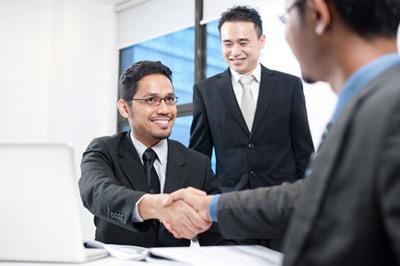 27614011-young-businessman-shaking-hand-with-businesswoman-in-front-of-colleague.jpg